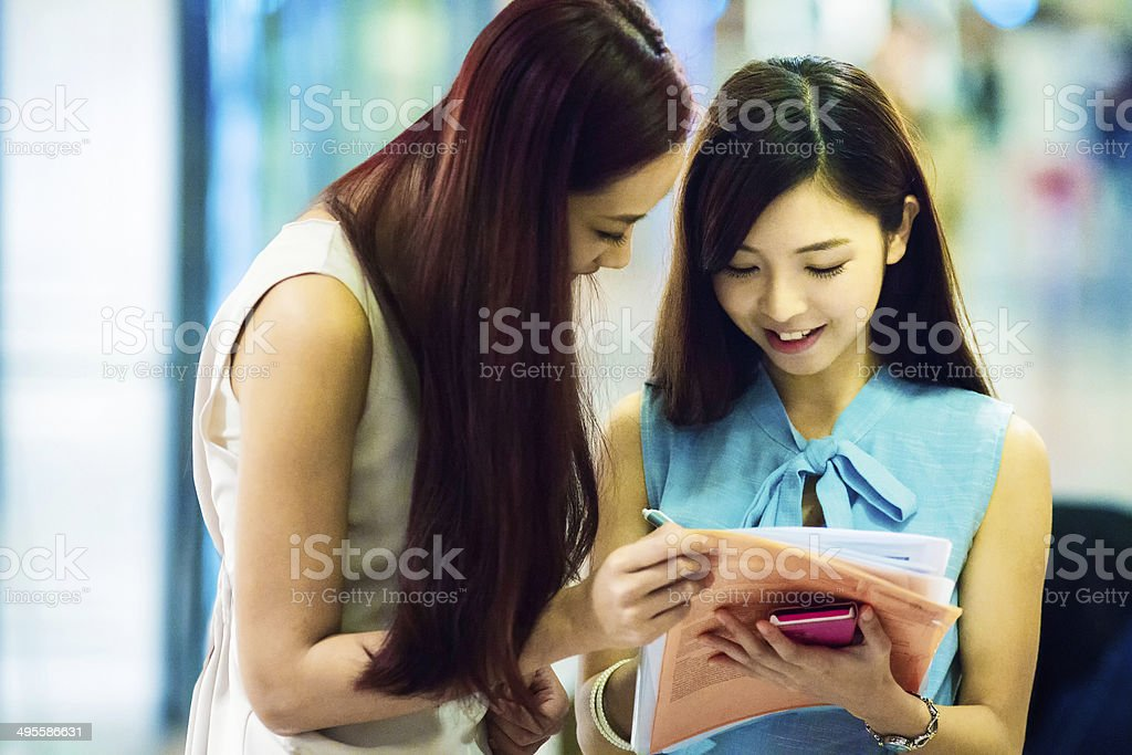 Young shopaholic women signing up for credit card stock photo