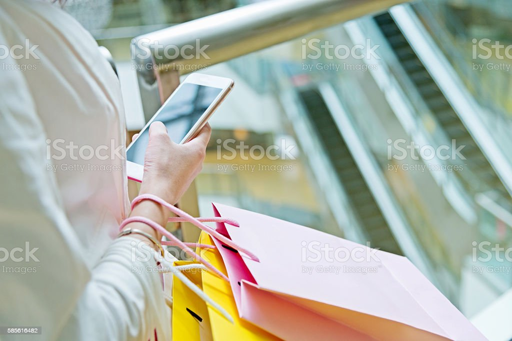 Young shopping woman using a smartphone stock photo
