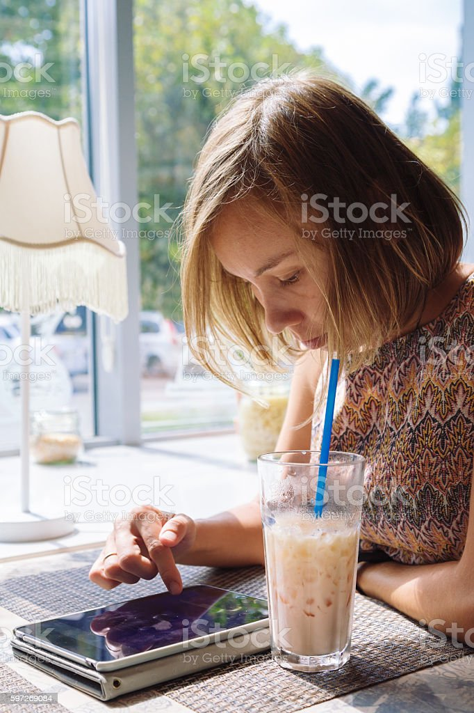 Young short-haired woman using tablet in cafe stock photo