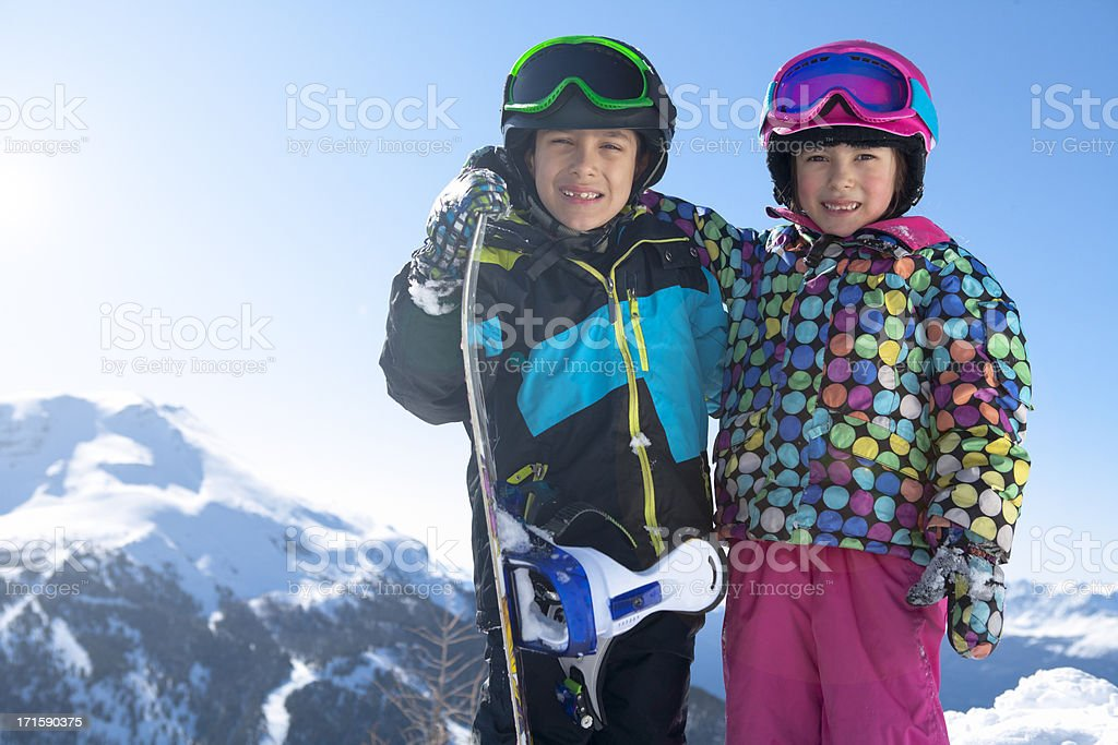 Young sibling snowboarder at the mountain stock photo