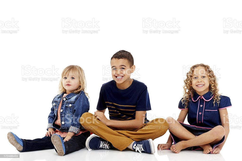 Young siblings sitting together on white background royalty-free stock photo