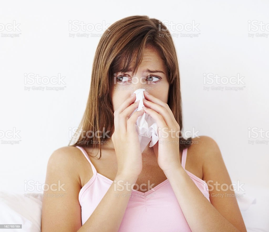 Young sick woman blowing her nose and looking away royalty-free stock photo