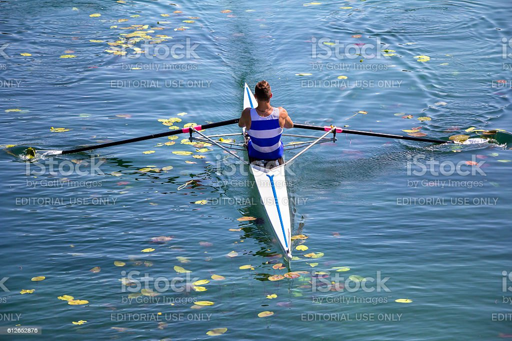 Young single scull rowing competitor paddles on the tranquil l stock photo