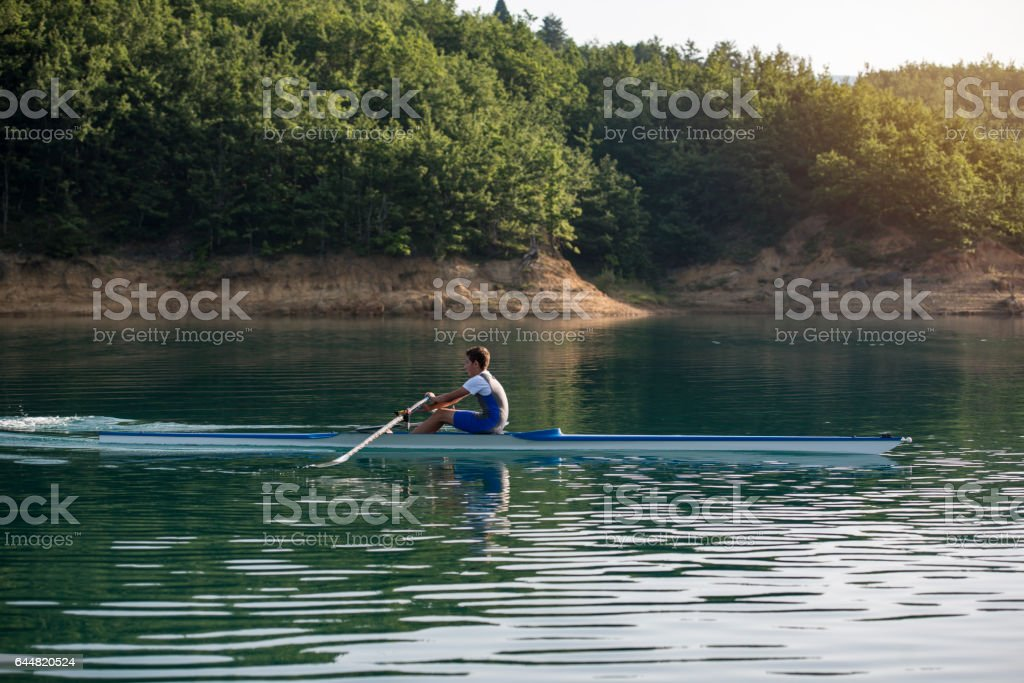 A Young single scull rowing competitor stock photo