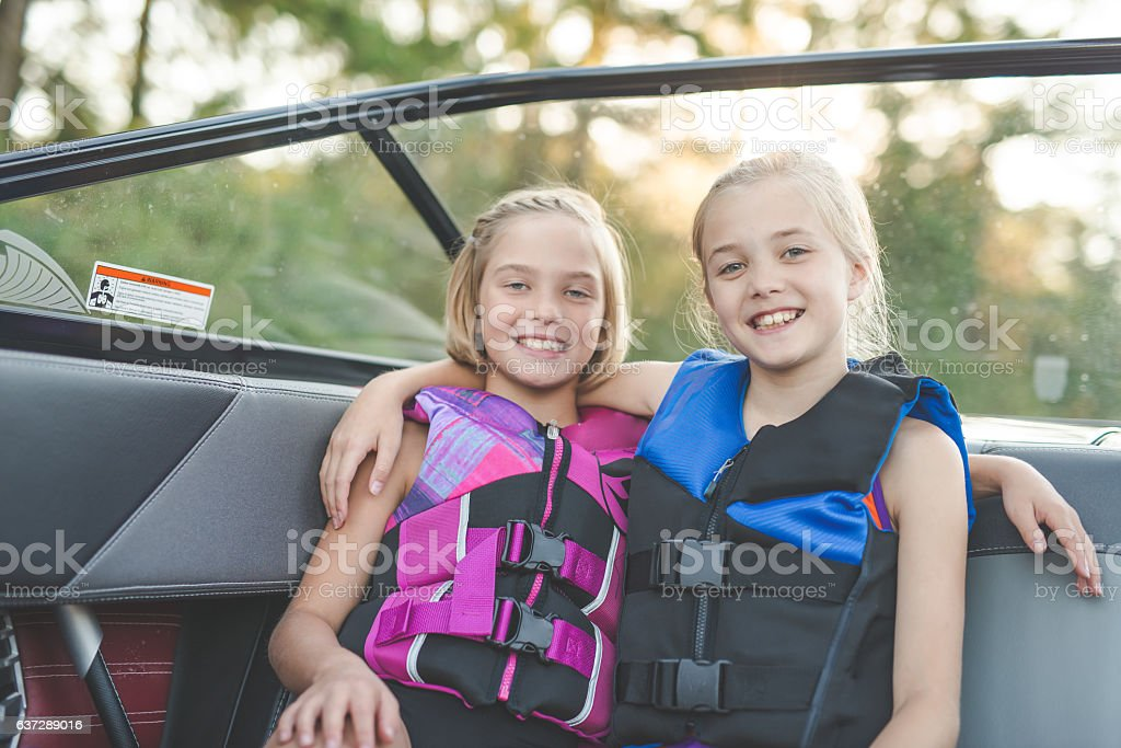 Young sisters on a boat in lifejackets smiling at camera stock photo