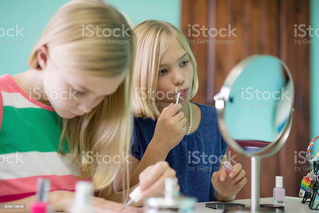 Young sisters playing dress up and using lip gloss stock photo