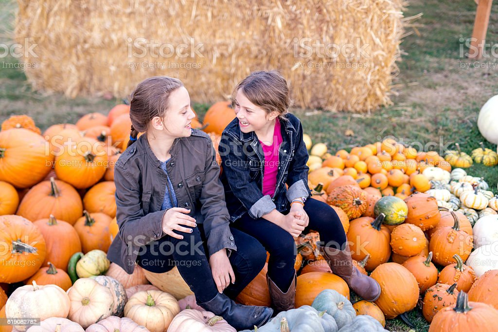 Young sisters sitting on a pile of pumpkins and talking stock photo