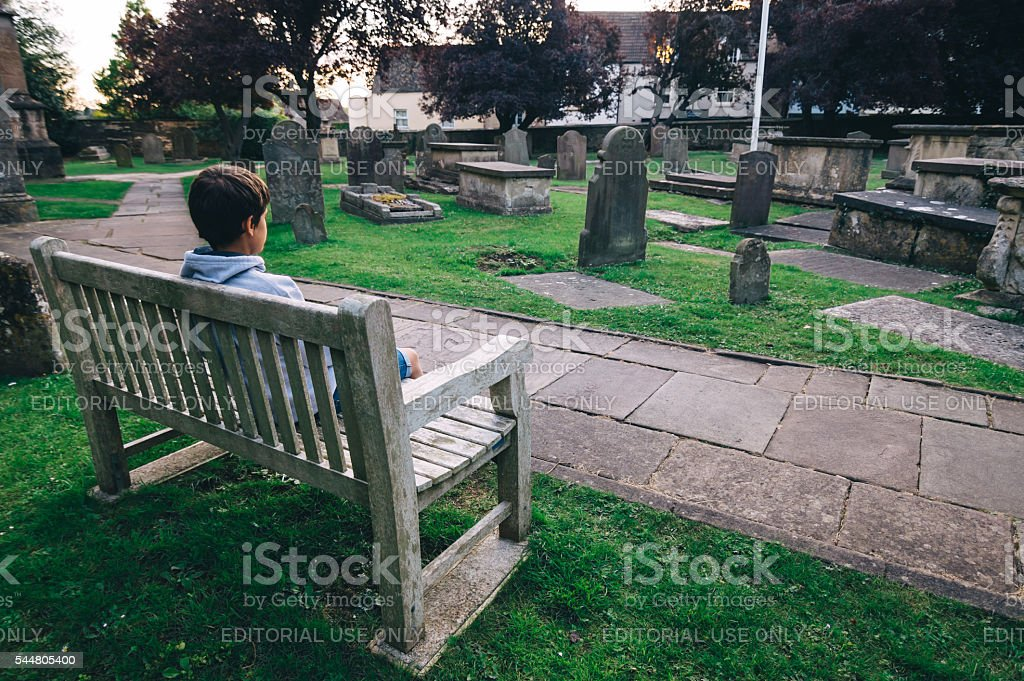 Young sitting at the churchyard stock photo