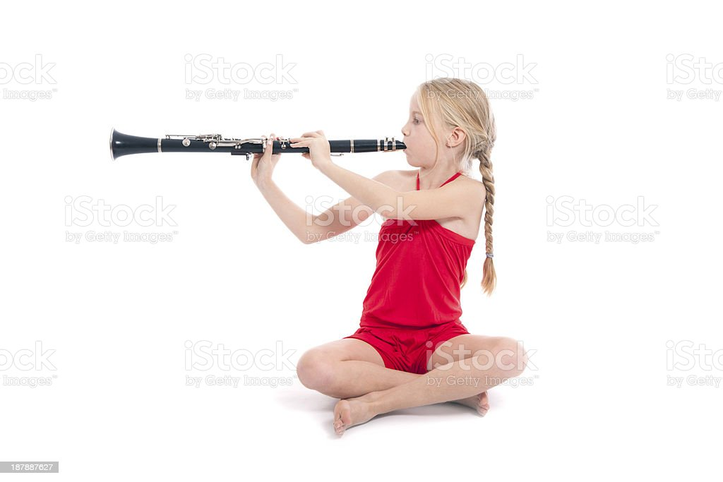 young sitting girl in red playing clarinet stock photo