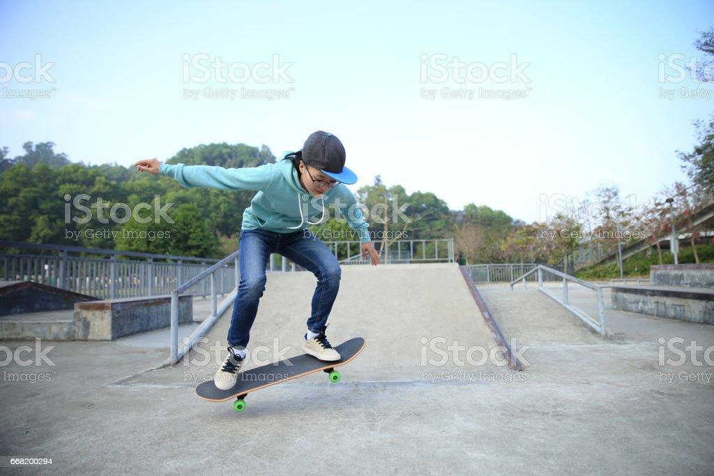 young skateboarder legs riding skateboard at skatepark stock photo
