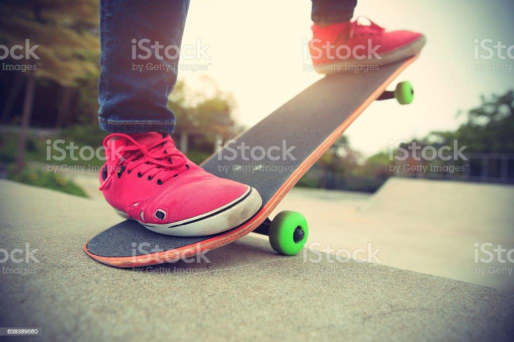 young skateboarder legs skateboarding at skatepark stock photo