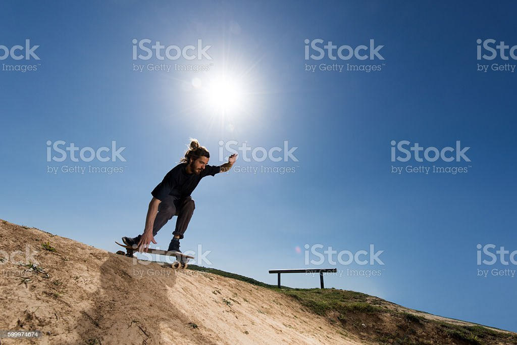 Young skateboarder on a dirt road about to go downhill. stock photo