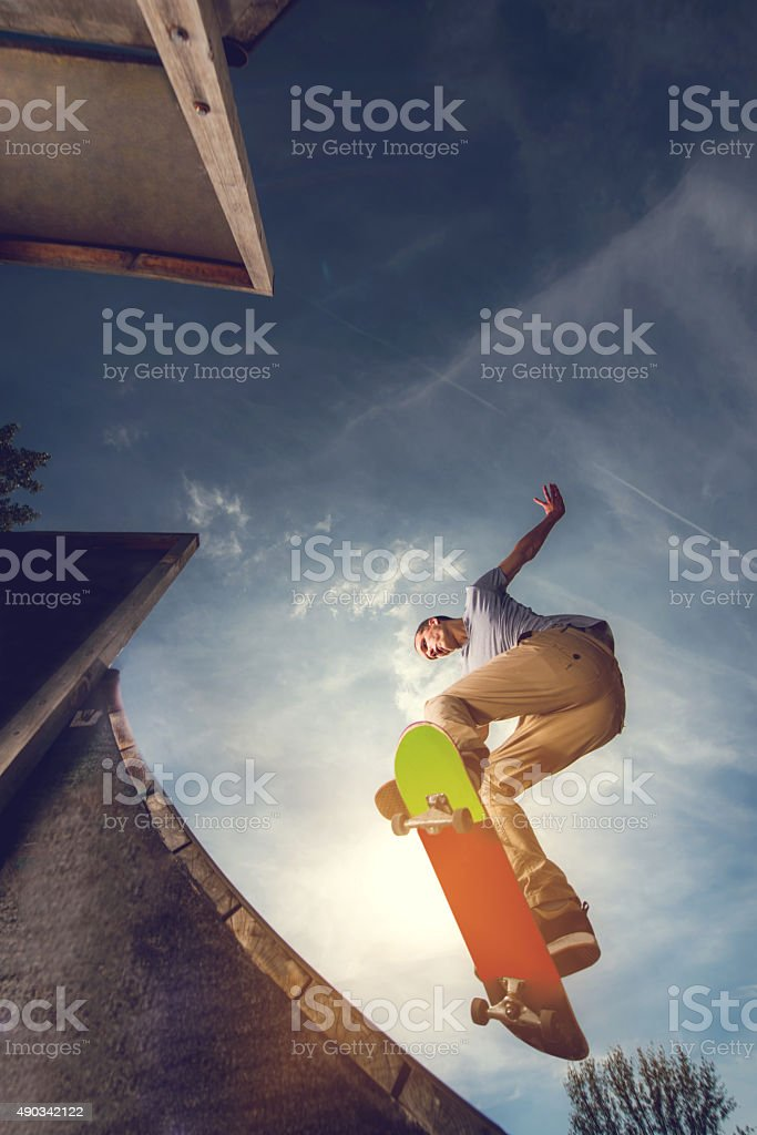 Young skateboarder on a skate ramp against the sky. stock photo