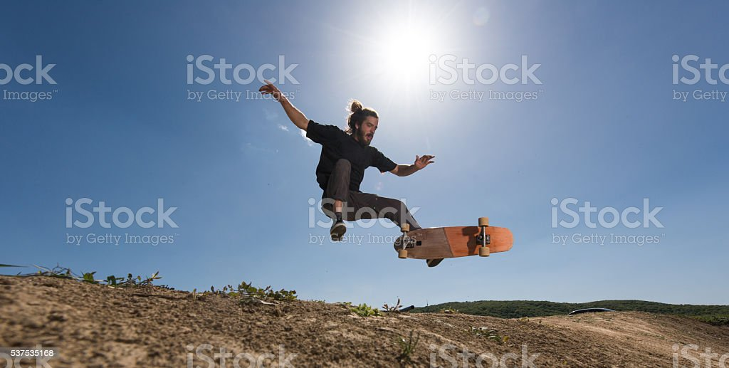 Young skateboarder practicing Ollie against the blue sky. stock photo