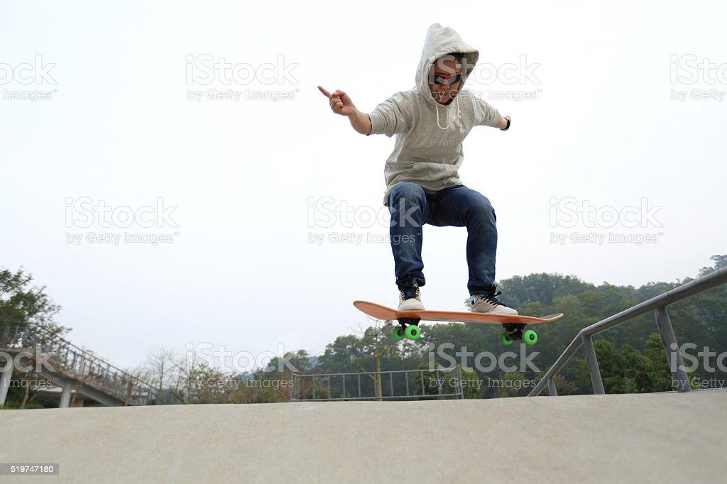 young skateboarder skateboarding at skatepark stock photo