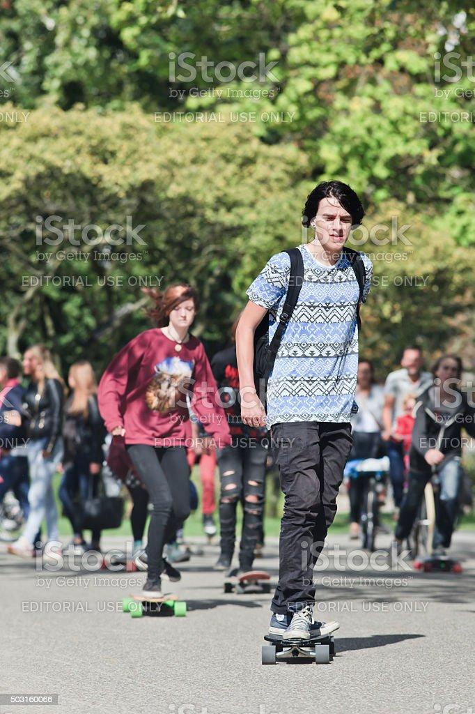 Young skateboarders having fun in a sunlit Amsterdam Vondelpark stock photo