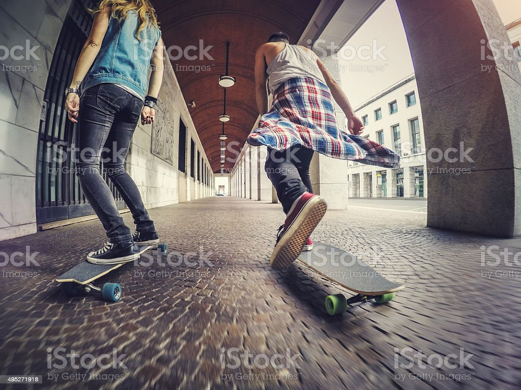 Young skaters riding longboard skateboards stock photo
