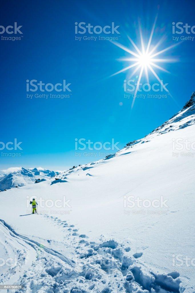 Young skier on slope of ski resort walking stock photo