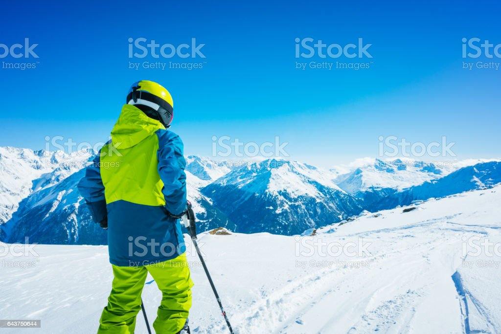 Young skier skiing down the slope of ski resort stock photo