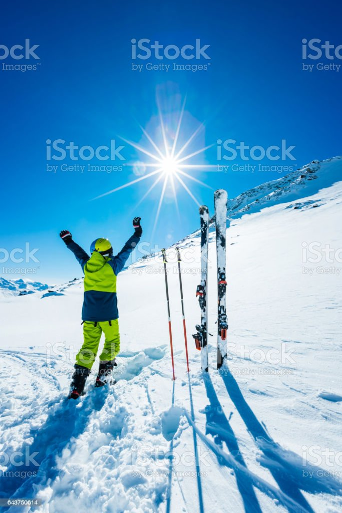 Young skier with hands in the air stock photo
