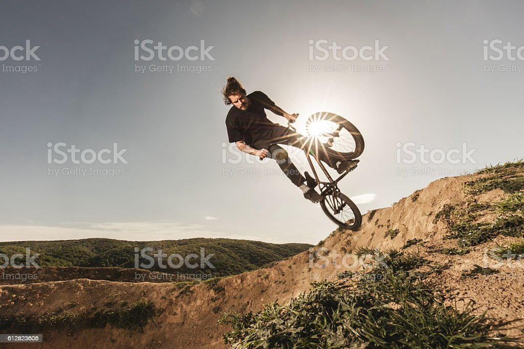 Young skilful cyclist in action on extreme terrain. stock photo