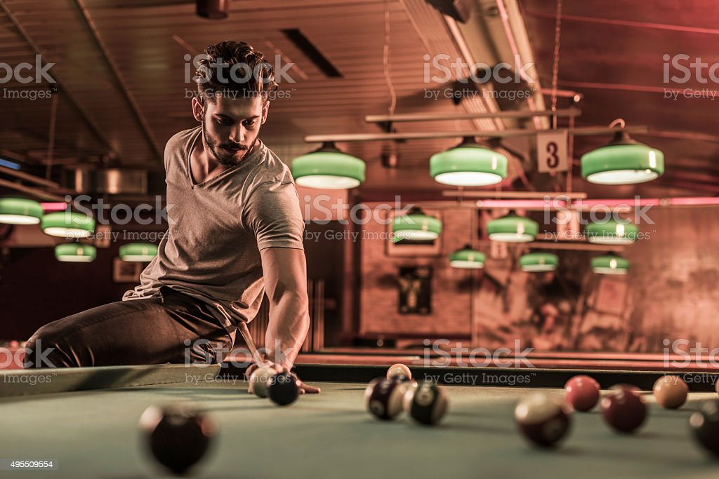 Young skillful man playing billiard in a pub. stock photo