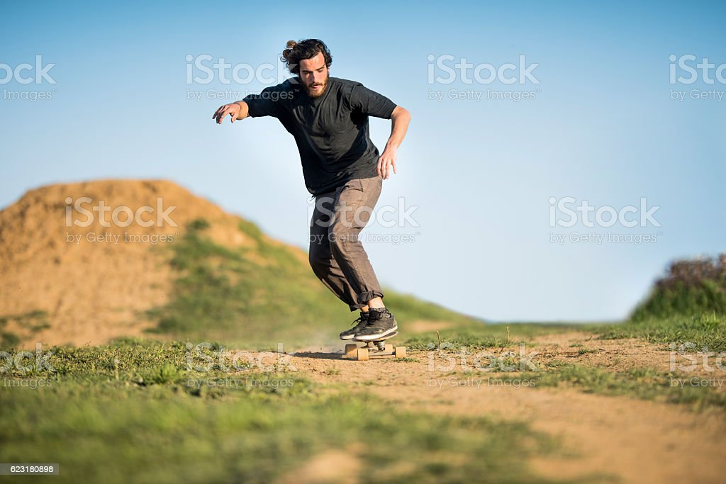 Young skillful skateboarder practicing on dirt road. stock photo