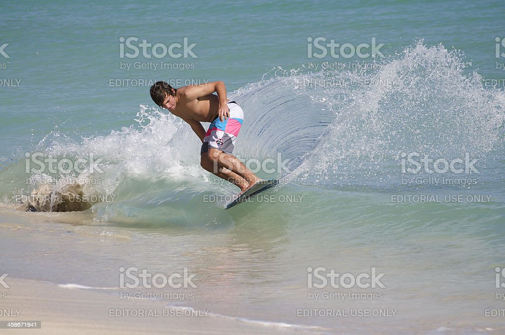Young Skimboarder Glides onto Miami Beach stock photo