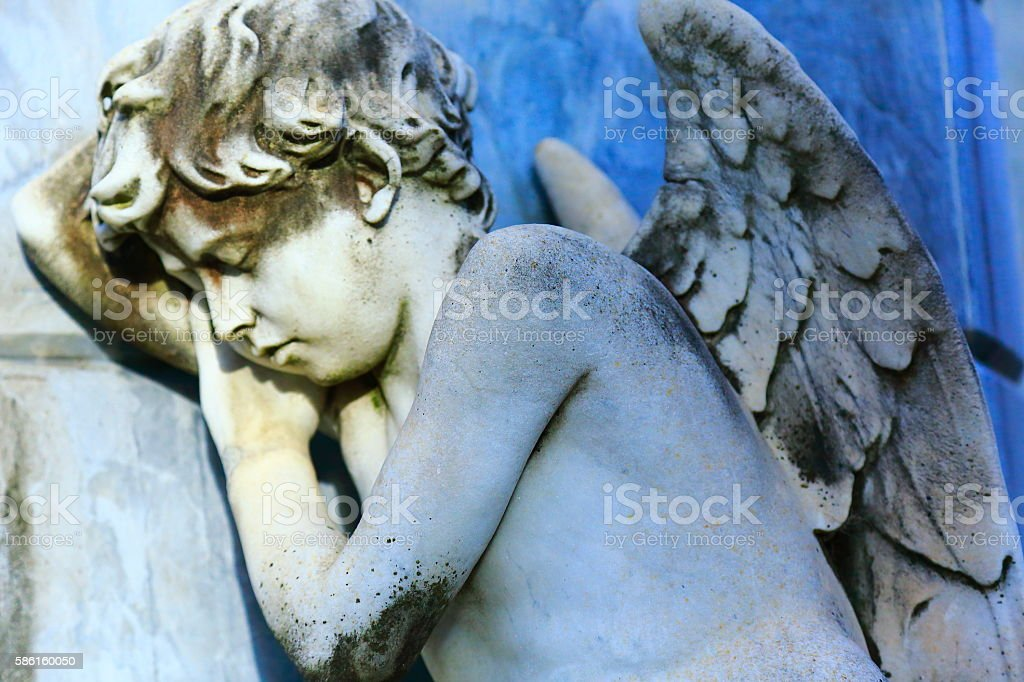 Young sleeping, sad Angel at sunrise, Recoleta cemetery, Buenos Aires stock photo