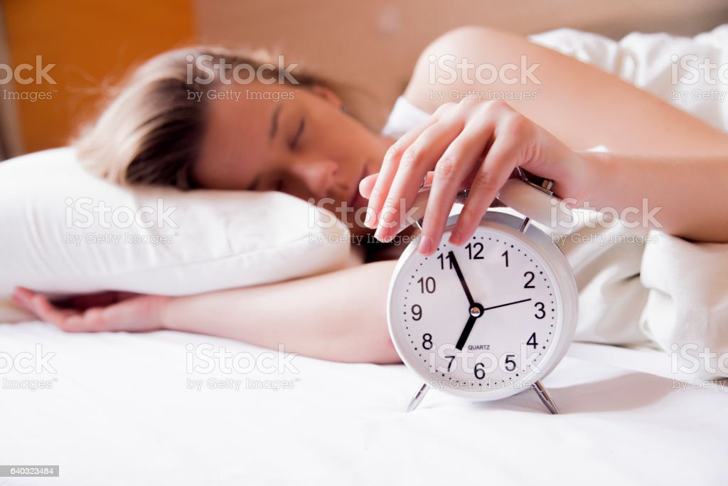 Young sleeping woman and alarm clock in bedroom at home stock photo