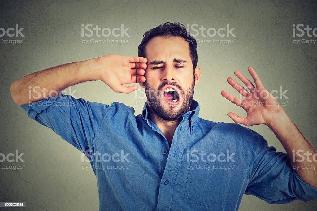 Young sleepy man yawning stretching arms back stock photo