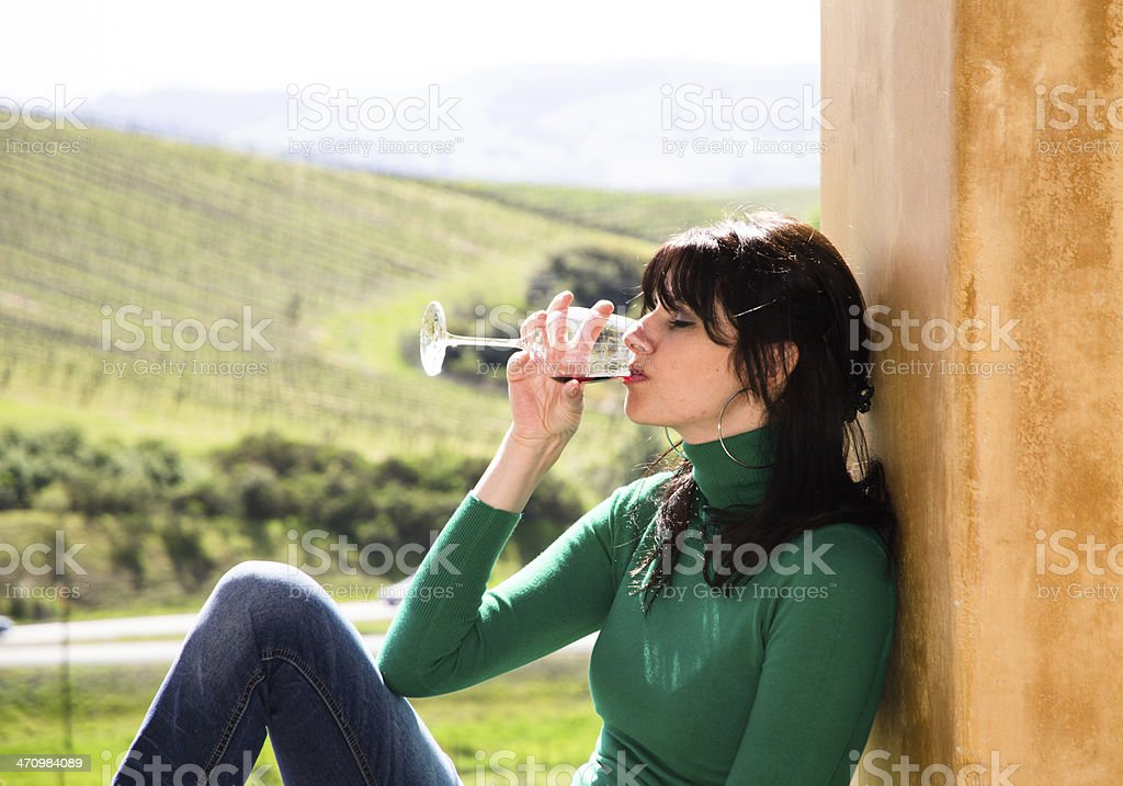 Young slim caucasian woman enjoys glass of wine outdoors stock photo