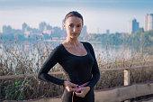 Young slim fitness woman measures her waistline outdoor