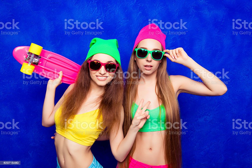 Young slim girls holding skateboard and gesturing with two fingers stock photo
