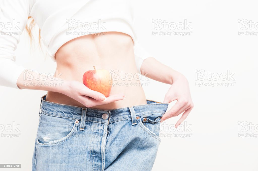 Young slim woman holding an apple and wearing oversize jeans stock photo
