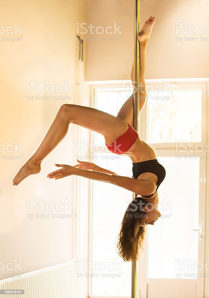 Young slim woman performing pole dance. stock photo