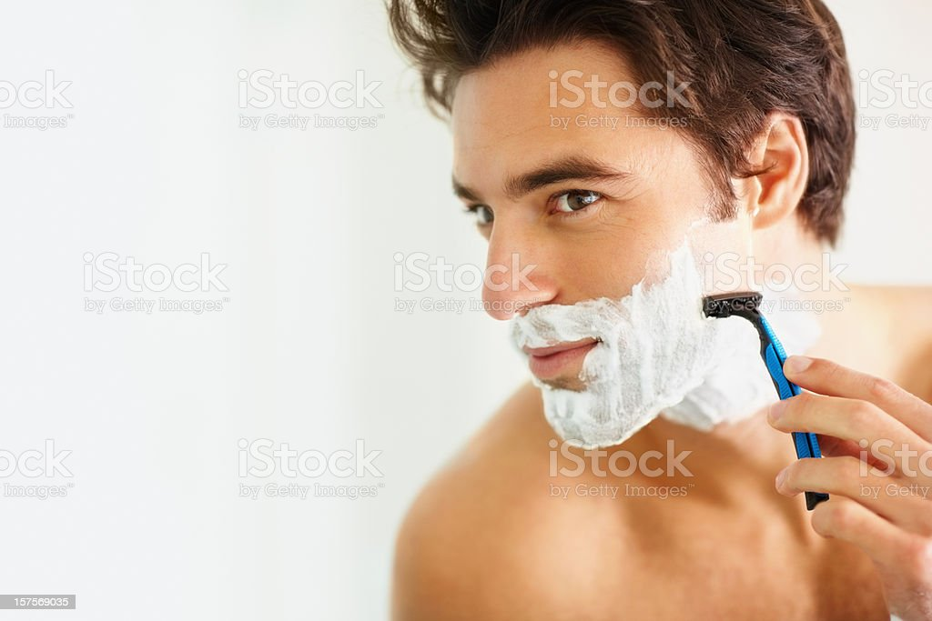 Young smart man shaving using a razor stock photo