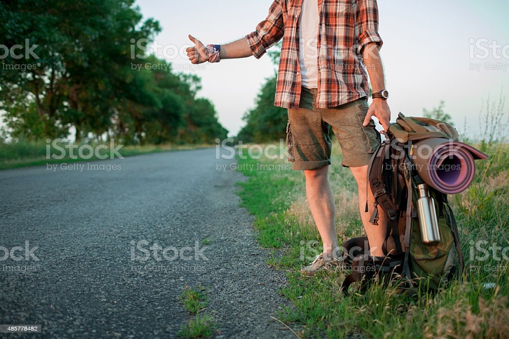 Young smilimg caucasian tourist hitchhiking along a road stock photo
