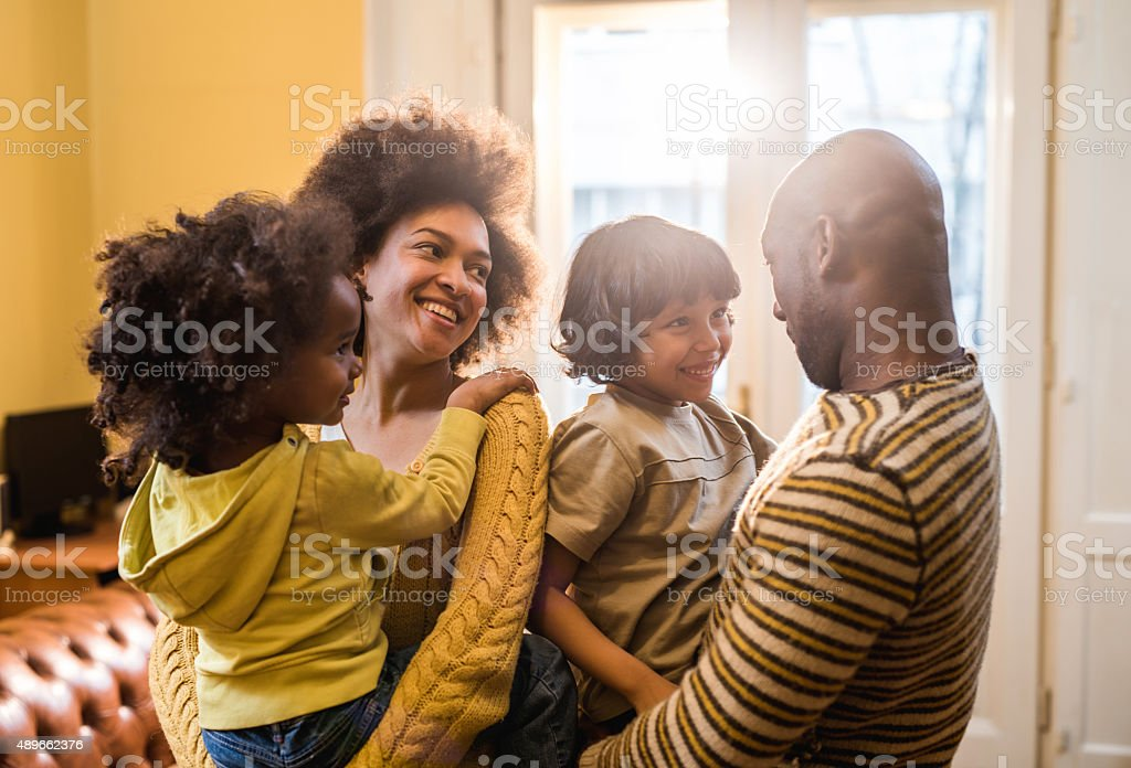 Young smiling African American family communicating among themselves. stock photo