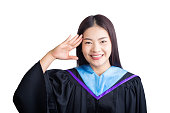 Young smiling asian female graduate student saluting