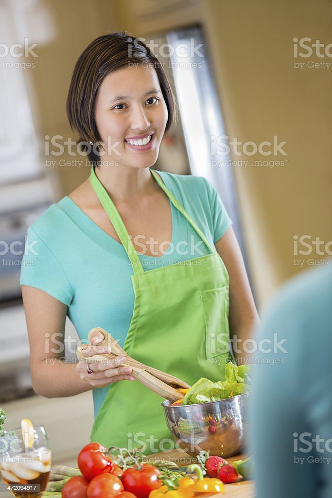 Young Smiling Asian Woman Mixing Salad in Kitchen royalty-free stock photo