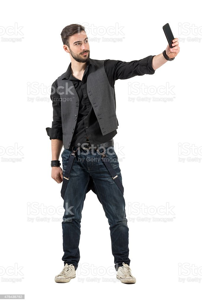 Young smiling bearded hipster taking selfie from high angle stock photo