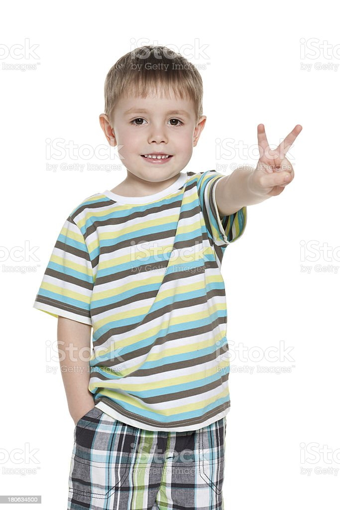 Young smiling boy shows victory sign royalty-free stock photo