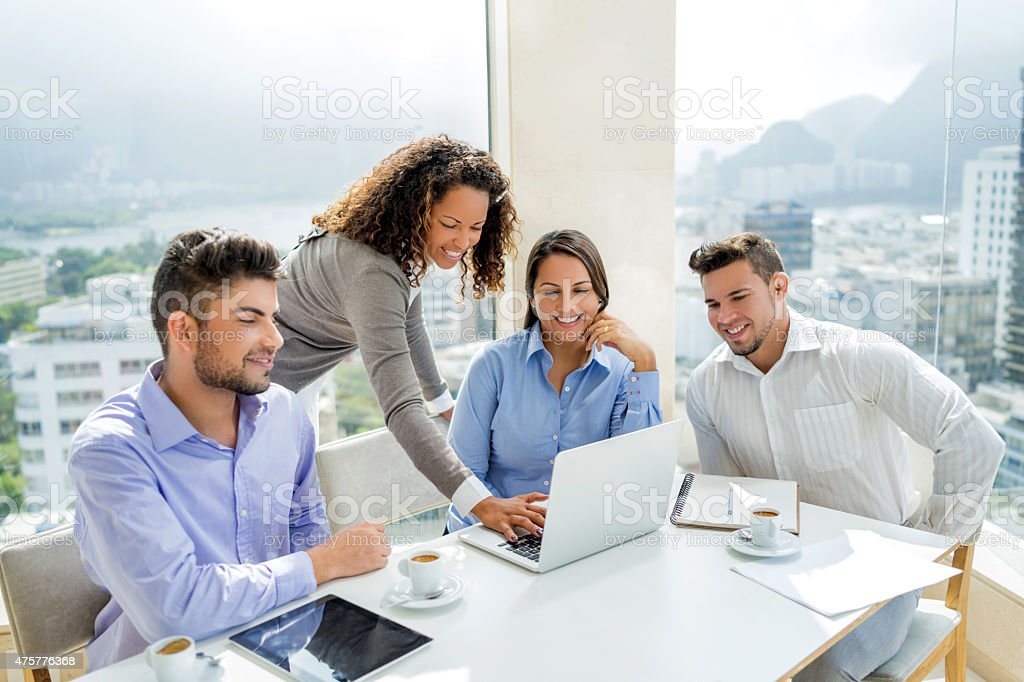 Young smiling business team working on laptop in the office. stock photo
