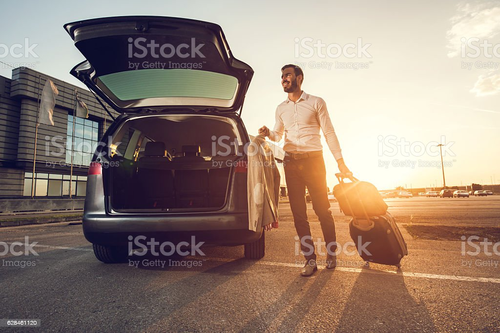 Young smiling businessman going on a business trip. stock photo