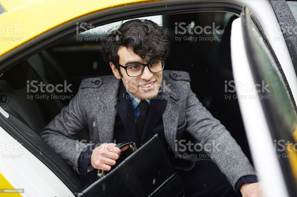 Young Smiling Businessman Leaving Taxi in Rain stock photo