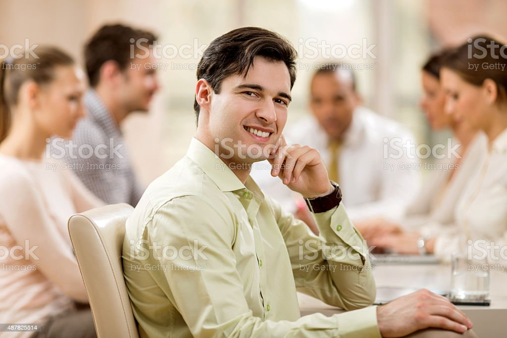 Young smiling businessman on a meeting looking at camera. stock photo