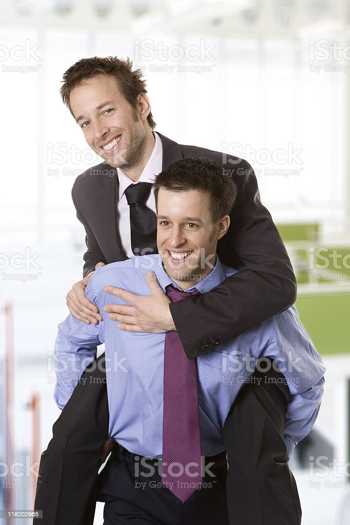 Young smiling businessman piggybacking his colleague stock photo