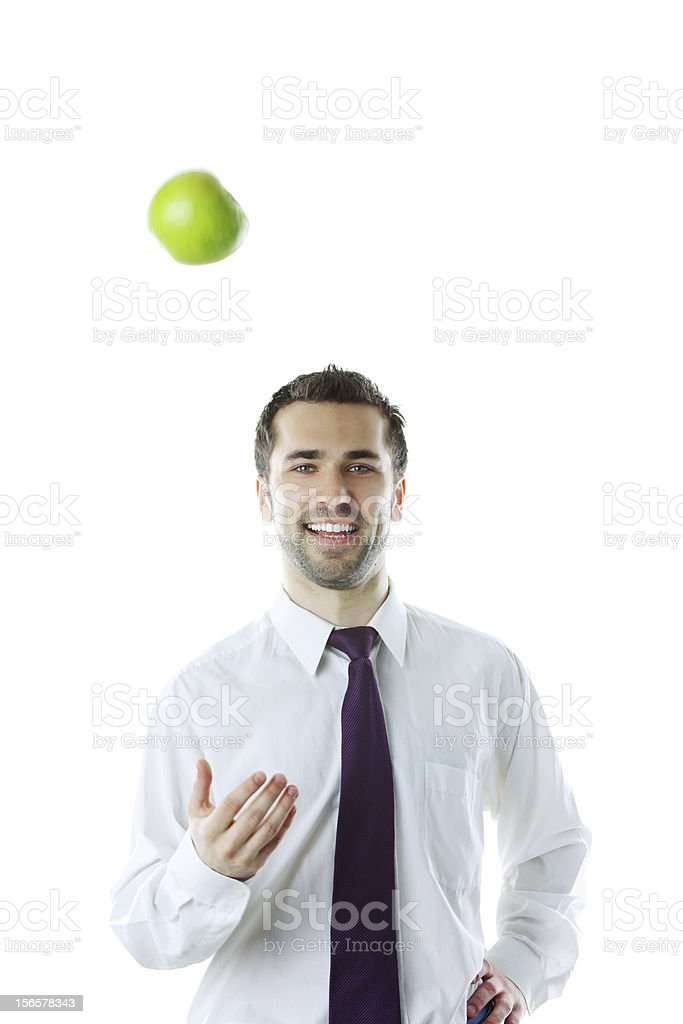 Young smiling businessman throwing up an apple royalty-free stock photo