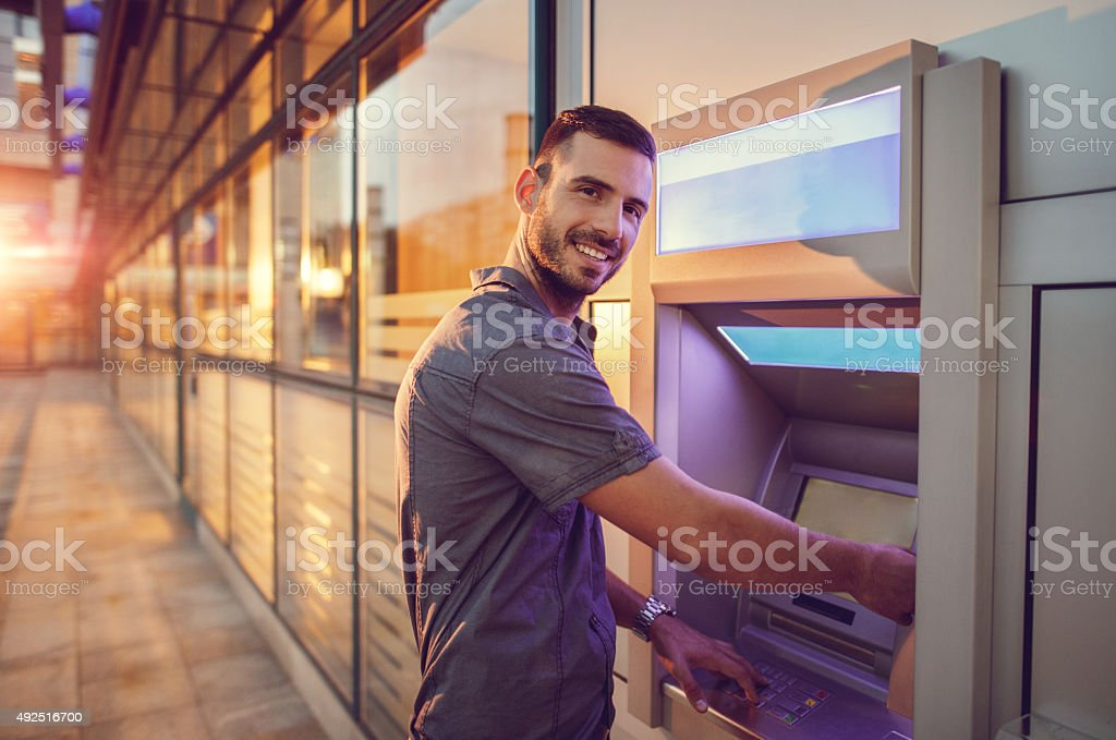 Young smiling businessman withdrawing money from ATM. stock photo